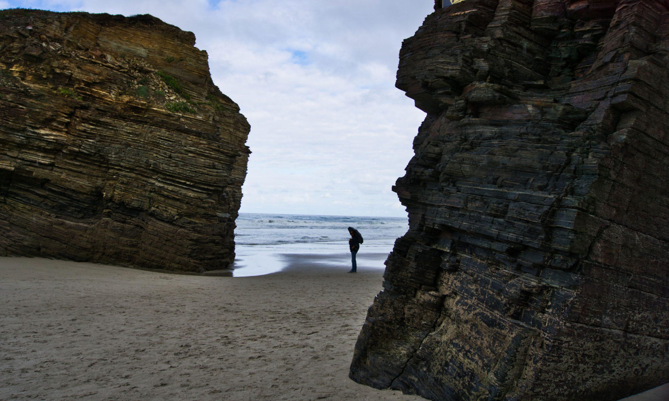 човек с чадър на плажа